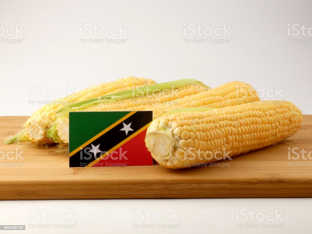 Saint Kitts and Nevis flag on a wooden panel with corn isolated on a white background stock photo