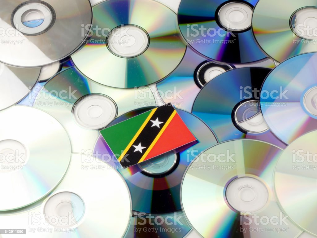 Saint Kitts and Nevis flag on top of CD and DVD pile isolated on white stock photo