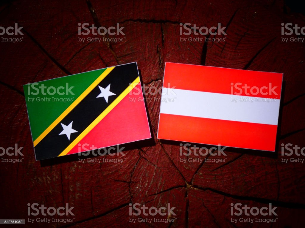 Saint Kitts and Nevis flag with Austrian flag on a tree stump isolated stock photo