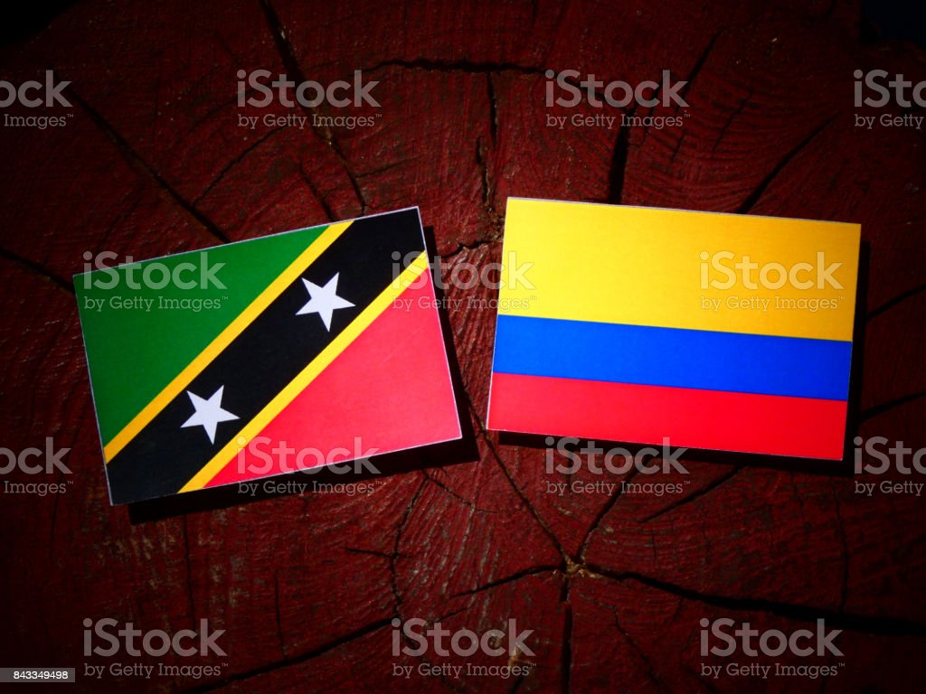 Saint Kitts and Nevis flag with Colombian flag on a tree stump isolated stock photo