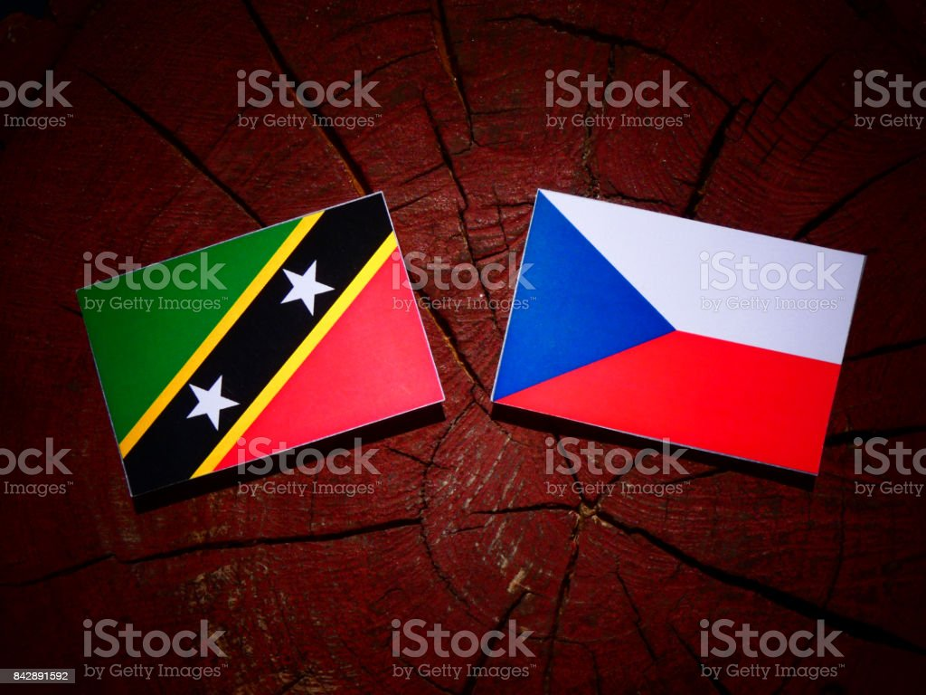 Saint Kitts and Nevis flag with Czech flag on a tree stump isolated stock photo