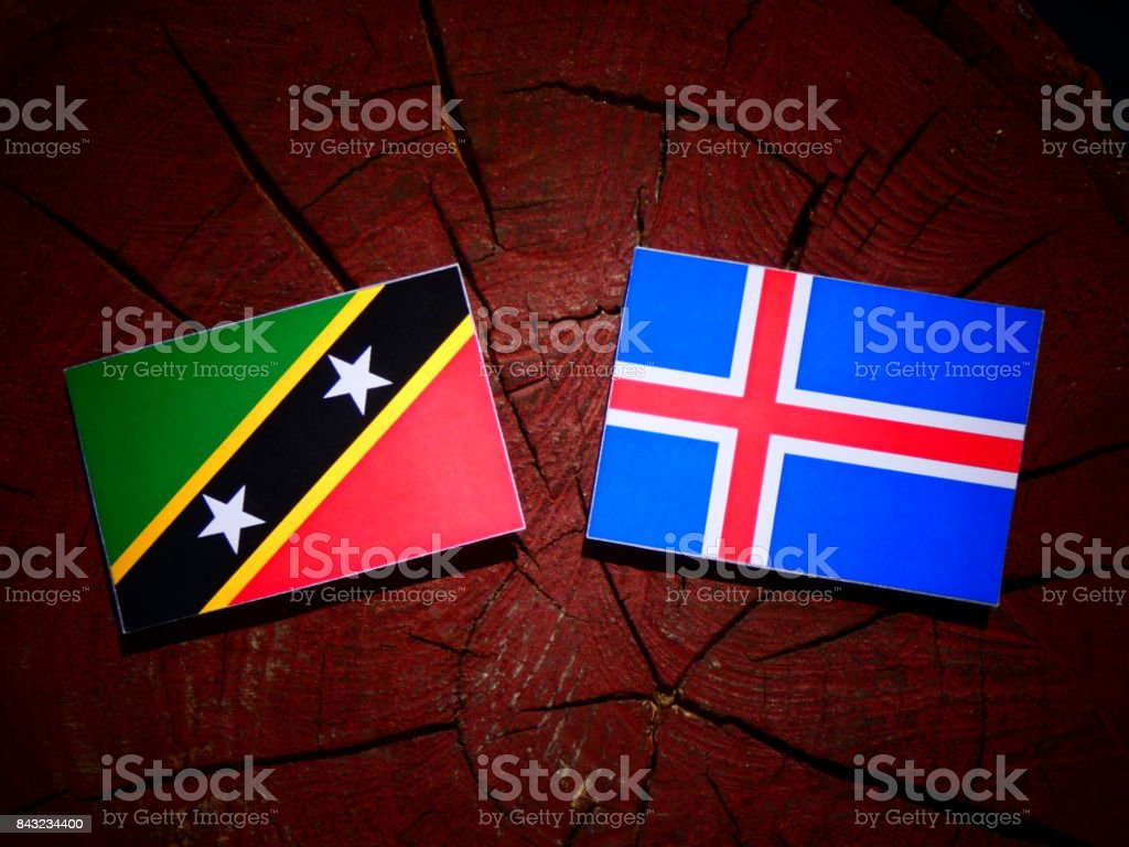 Saint Kitts and Nevis flag with Icelandic flag on a tree stump isolated stock photo