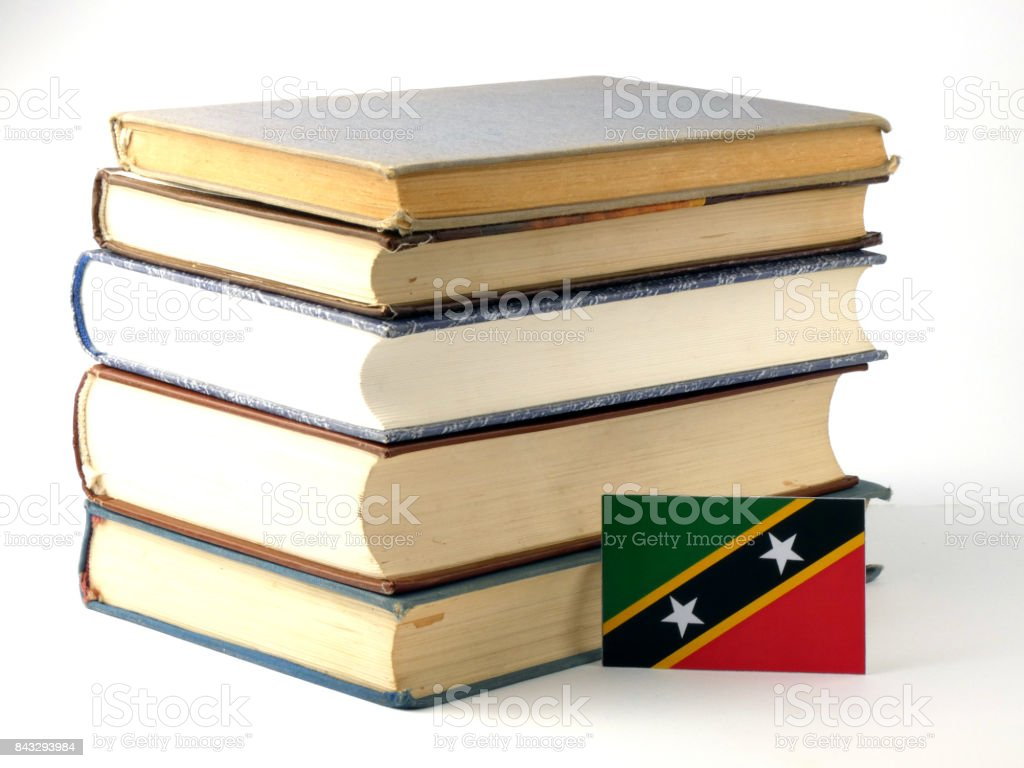 Saint Kitts and Nevis flag with pile of books isolated on white background stock photo
