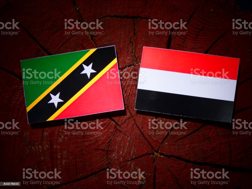 Saint Kitts and Nevis flag with Yemeni flag on a tree stump isolated stock photo