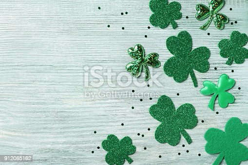 Saint Patricks Day background with green confetti and shamrock on white rustic board top view.