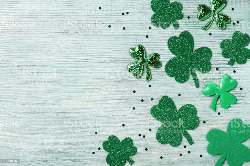 Saint Patricks Day background with green shamrock on white rustic board top view. stock photo