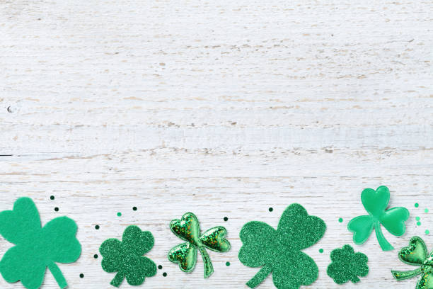 saint patricks day border with green shamrock on white rustic board from above. - st patricks day background stock photos and pictures
