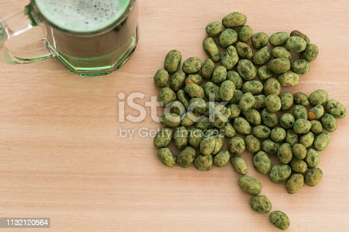 1124676977 istock photo Saint Patrick's day. Focused mug of green spilled beer and unfocused green peanuts forming a shamrock leaf on wooden board 1132120564