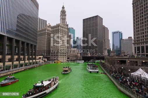 Chicago, USA – Mar 17, 2018: Early in the morning the River turned green by the plumbers local 130. Every Year following tradition they pour orange dye that turns the river green for the annual Saint Patrick's Day celebration. The tradition stretches back to 1962 when Mayor Daley was trying to get to the bottom of the pollution problem in the Chicago river. They developed a green dye that would show the dumping was occurring. It developed into a long standing celebration and tradition. Hundreds of thousands of people crowd the river every year to watch.