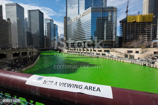 Chicago, USA – Mar 17, 2018: Early in the morning a Not A Viewing Area sign on the Dusable Bridge after the River was turned green by the plumbers local 130. Every Year following tradition they pour orange dye that turns the river green for the annual Saint Patrick's Day celebration. The tradition stretches back to 1962 when Mayor Daley was trying to get to the bottom of the pollution problem in the Chicago river. They developed a green dye that would show the dumping was occurring. It developed into a long standing celebration and tradition. Hundreds of thousands of people crowd the river every year to watch.