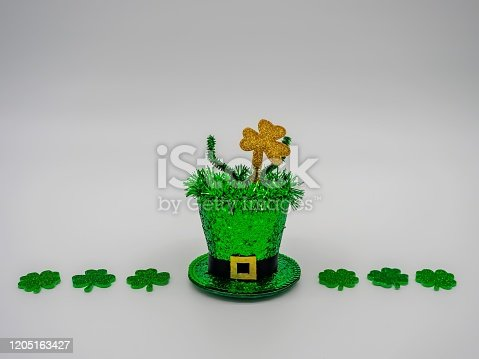 Saint Patrick's Day Sparkly Green Hat with Glittery Four Leaf Clovers Lined up Next to it in a Line on a White Background!