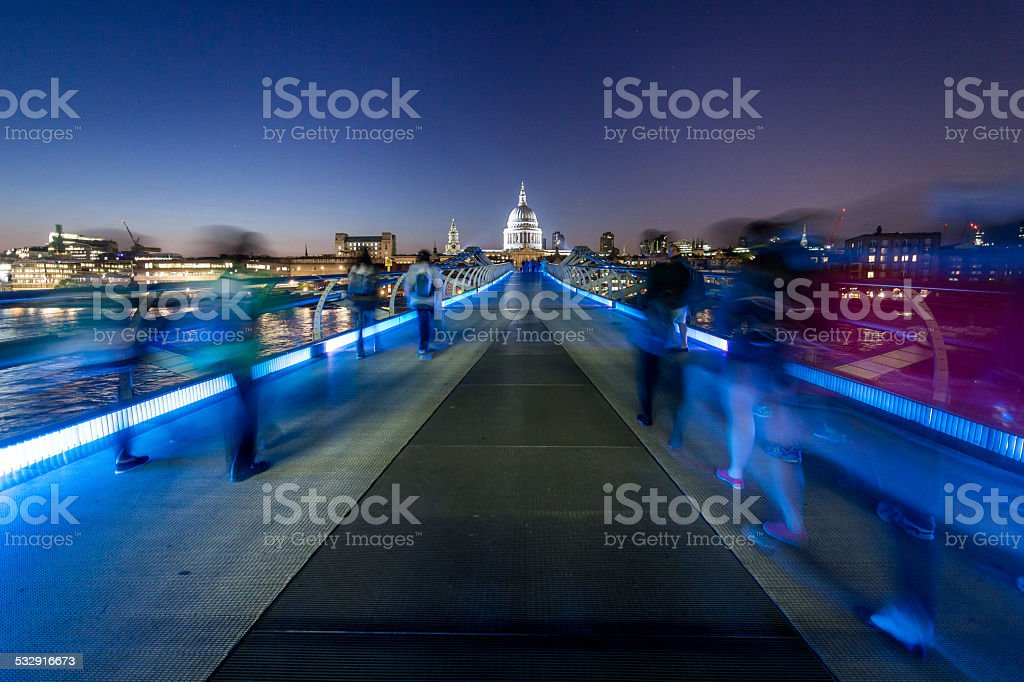 Saint Paul's Cathedral and tourists walking on Millenium Bridge night stock photo