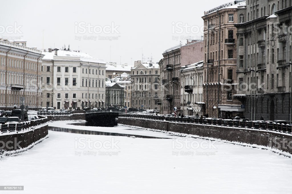 Saint Petersburg, Russia: the Moika river embankment by a winter day covered by ice and snow with old architecture historical buildings around. stock photo