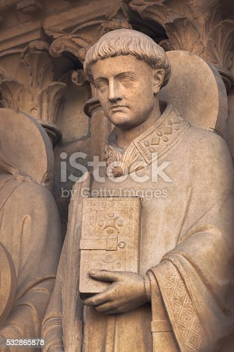 A statue portraying Saint Stephen, the first christian martyr, by one of the entrances, the Portal of the Virgin (built in 1210s-1220s), to Notre Dame cathedral in Paris.