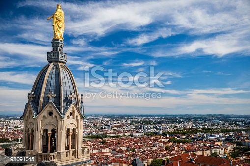 Beautiful Saint Thomas chapel aerial view with golden Virgin Mary statue on top of the steeple seen from the roofs of Basilica Notre Dame de Fourviere built between 1872 and 1884, in a dominant position overlooking the city of Lyon, and dedicated to the Virgin Mary. This image was taken during a sunny summer day in famous Lyon city in Rhone department, Auvergne-Rhone-Alpes region in France (Europe), outside Basilica Notre Dame de Fourviere, on Fourviere hill.