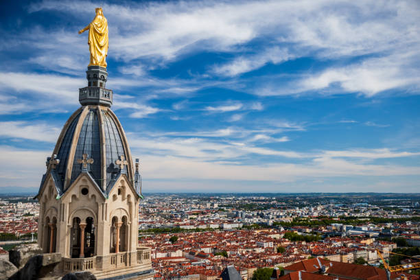 Saint Thomas chapel aerial view with golden Virgin Mary statue seen from the roofs of Basilica Notre Dame de Fourviere with Lyon French city in background Beautiful Saint Thomas chapel aerial view with golden Virgin Mary statue on top of the steeple seen from the roofs of Basilica Notre Dame de Fourviere built between 1872 and 1884, in a dominant position overlooking the city of Lyon, and dedicated to the Virgin Mary. This image was taken during a sunny summer day in famous Lyon city in Rhone department, Auvergne-Rhone-Alpes region in France (Europe), outside Basilica Notre Dame de Fourviere, on Fourviere hill. bell tower tower stock pictures, royalty-free photos & images