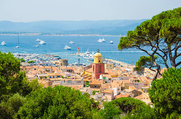 Saint Tropez town impression Looking from a viewpoint at the view of the town of Saint Tropez in France. St Tropez is a popular French summer holiday resort. The colour image was taken on a hot summer day. St.-Tropez is a coastal town on the French Riviera, in the Provence-Alpes-Côte d'Azur region of southeastern France. Long popular with artists, the town attracted the international