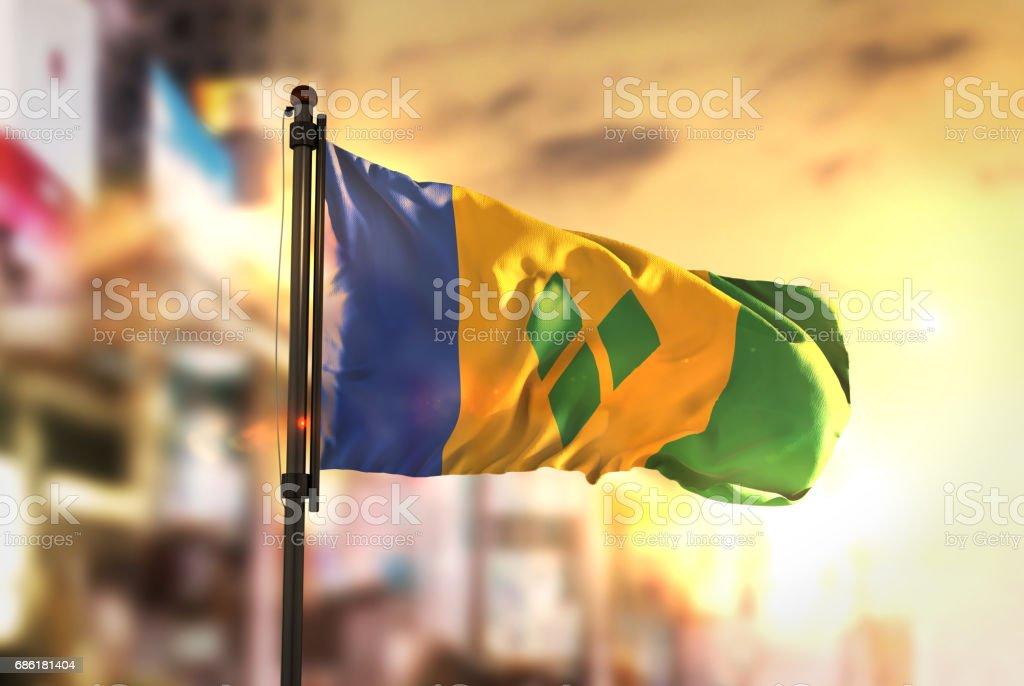 Bandeira de São Vicente e Granadinas contra cidade turva fundo no Sunrise Backlight - foto de acervo