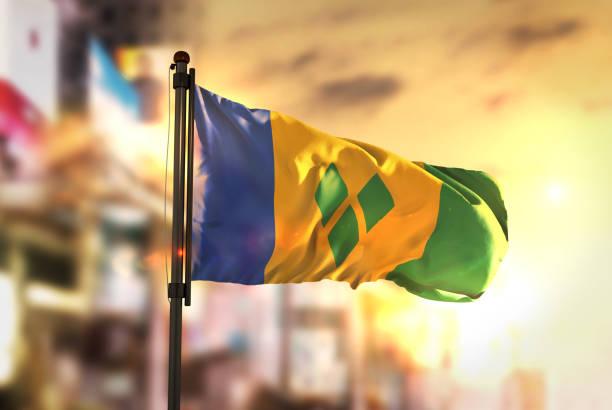 st. vincent und die grenadinen flagge gegen city unscharf hintergrund bei sonnenaufgang hintergrundbeleuchtung - kingstown stock-fotos und bilder