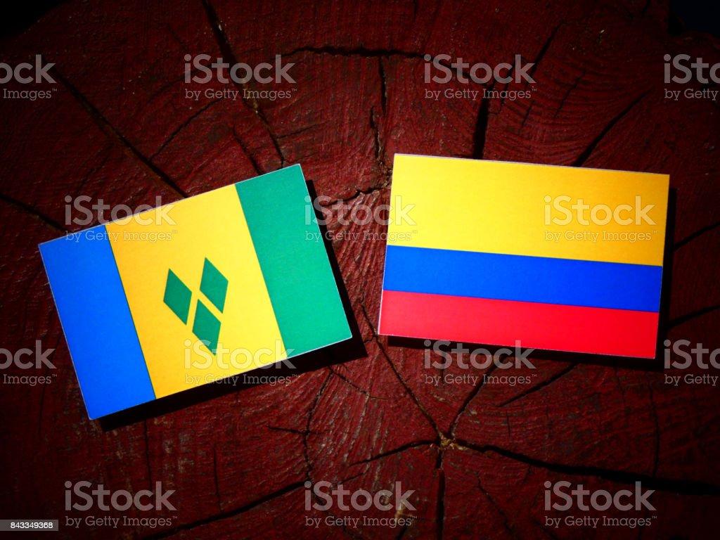 Bandeira de São Vicente e Granadinas com bandeira colombiana no tronco de uma árvore isolada - foto de acervo