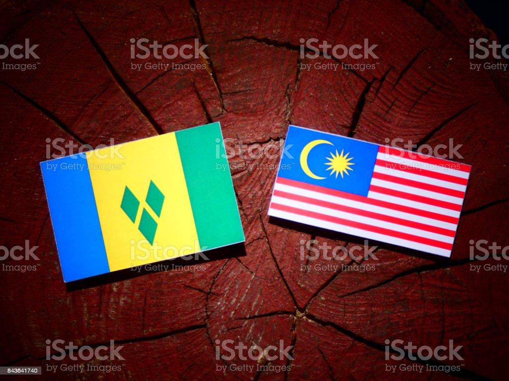 Bandeira de São Vicente e Granadinas com bandeira da Malásia em um toco de árvore isolada - foto de acervo