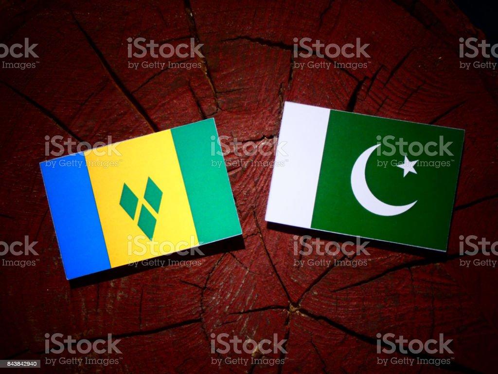 Bandeira de São Vicente e Granadinas com bandeira do Paquistão em um toco de árvore isolada - foto de acervo
