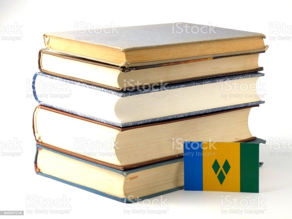 Bandeira de São Vicente e Granadinas com pilha de livros isolado no fundo branco - foto de acervo