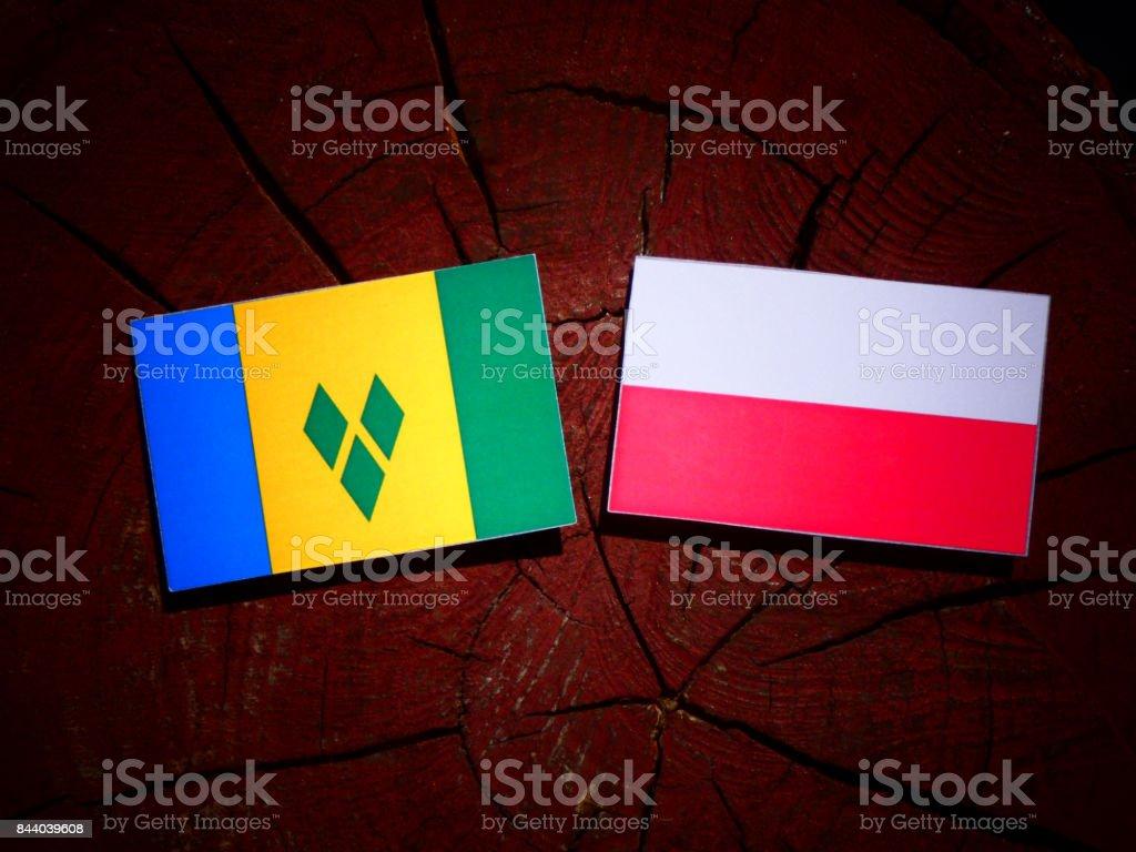 Bandeira de São Vicente e Granadinas com bandeira polonesa no tronco de uma árvore isolada - foto de acervo