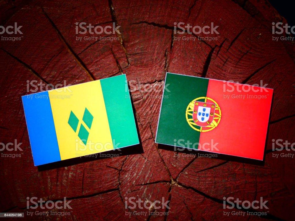 Bandeira de São Vicente e Granadinas com bandeira portuguesa no tronco de uma árvore isolada - foto de acervo