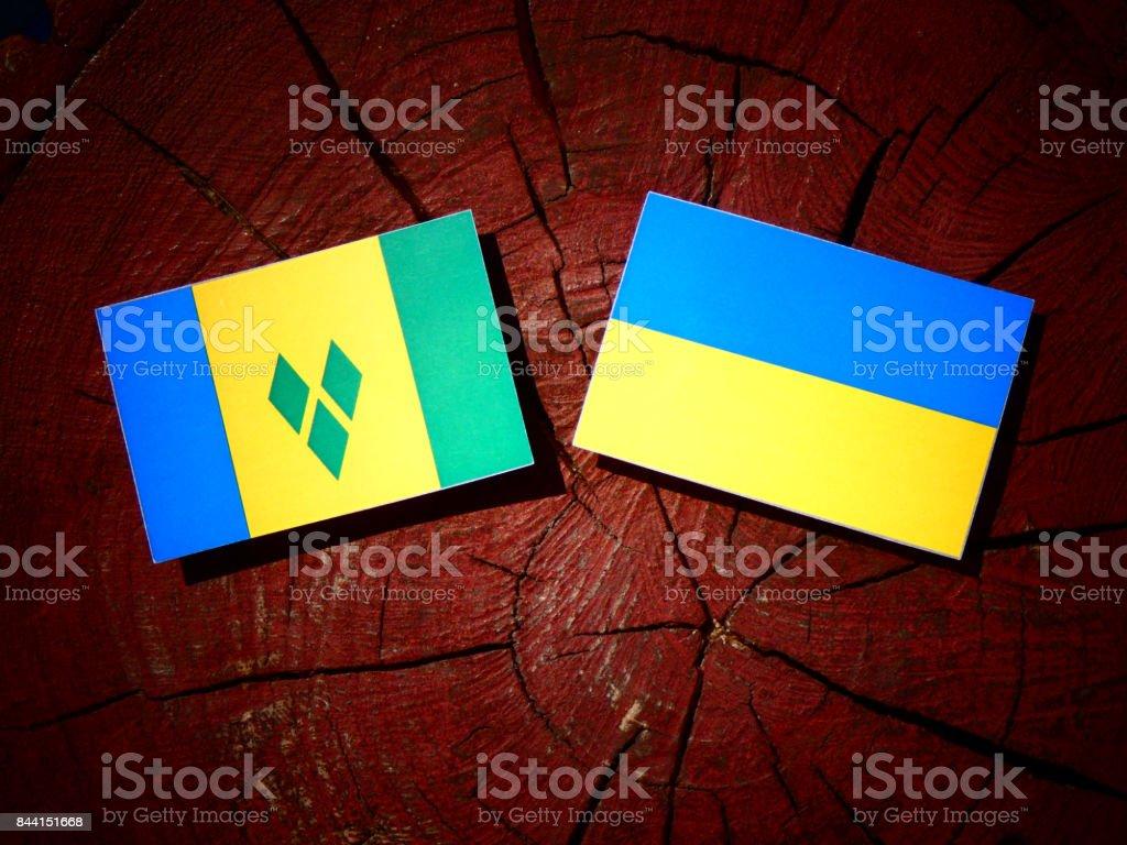 Bandeira de São Vicente e Granadinas com ucraniano bandeira em um toco de árvore isolado - foto de acervo