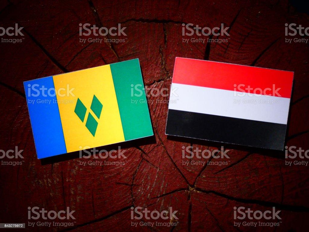 Bandeira de São Vicente e Granadinas com bandeira do Iémen no tronco de uma árvore isolada - foto de acervo