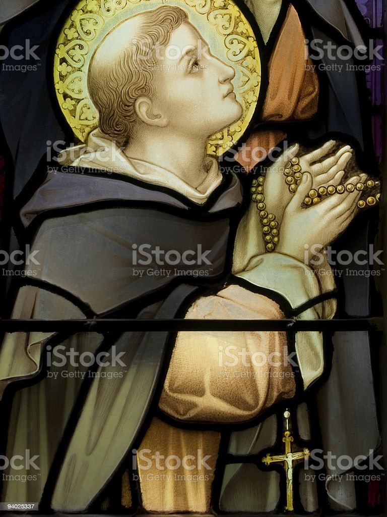 Saint with a rosary deep in prayer stock photo