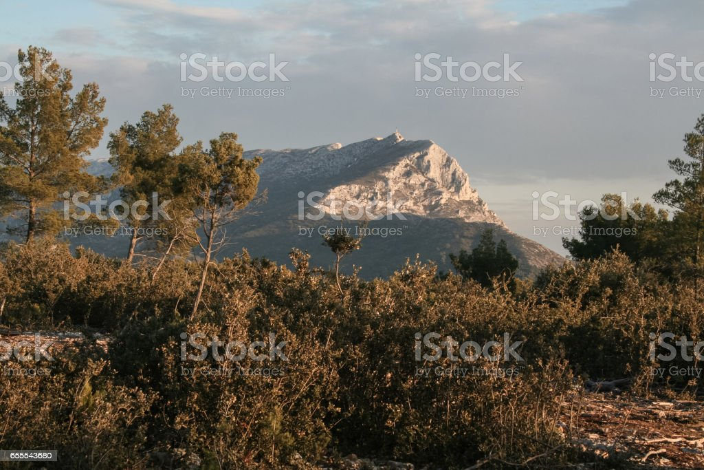 Sainte Victoire mount takent from its surrounding forest at sunset in winter. Sainte Victoire mountain is one of the symbols of the city of Aix-en-Provence, often painted by famous French painter Paul Cezanne stock photo