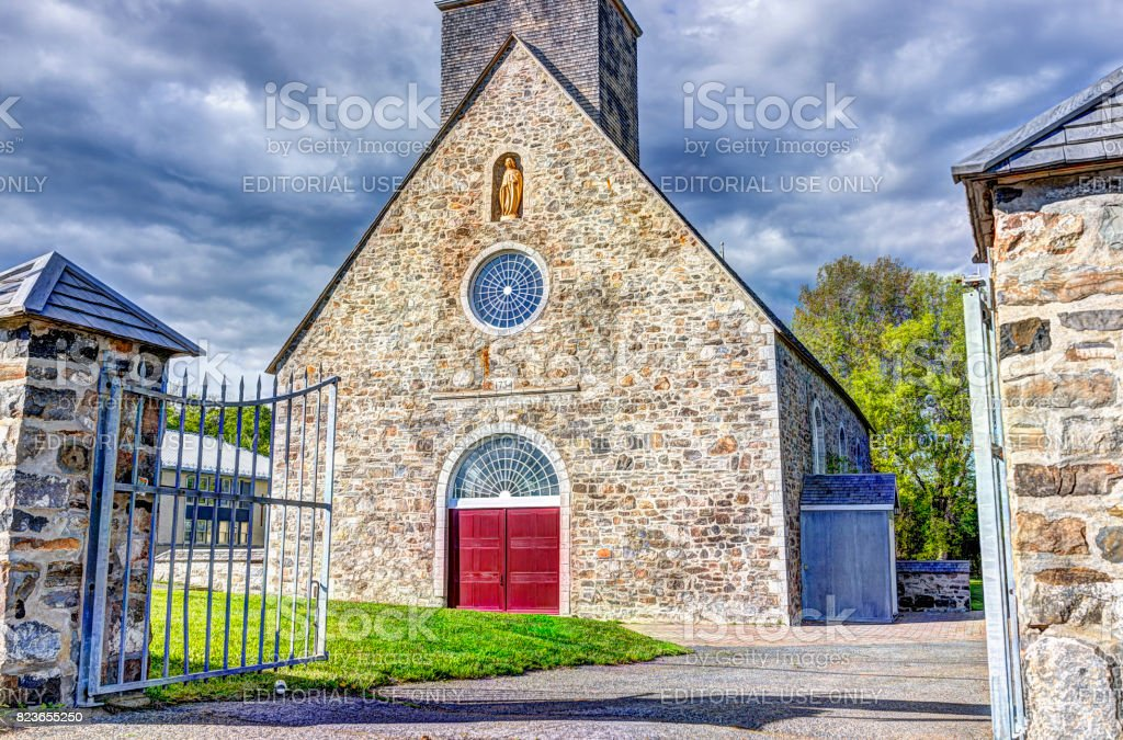 Saint-Francois red painted church with stone architecture and gold statue, blue sky in summer stock photo