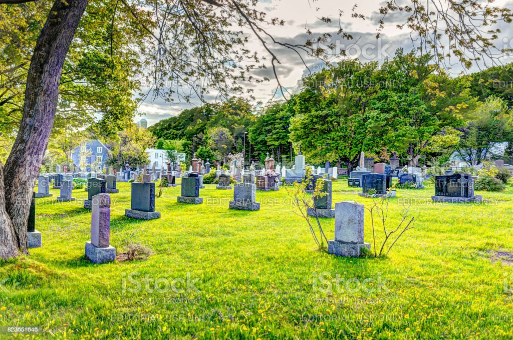 Saint-Jean church cemetery with stone gravestones and blue sky in summer stock photo