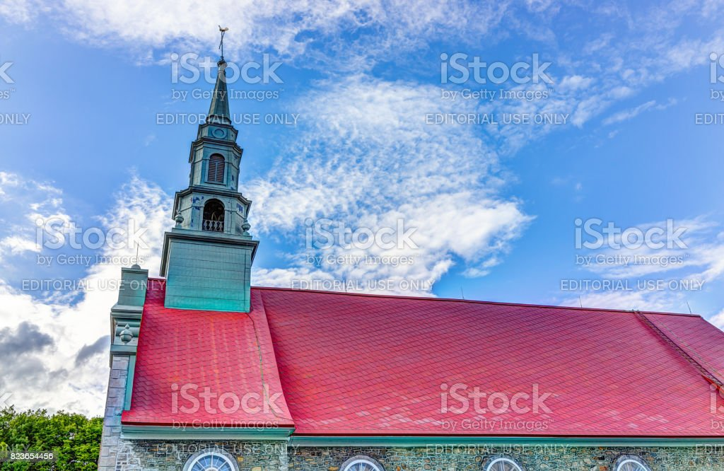 Saint-Jean red painted church with stone architecture and blue sky in summer stock photo