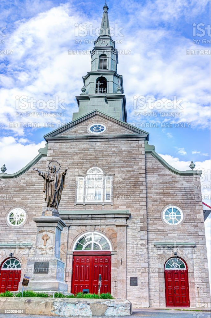 Saint-Jean red painted church with stone architecture and Jesus Christ statue, blue sky in summer stock photo