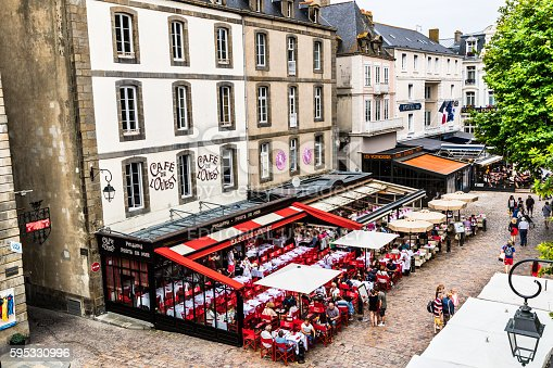 Saint-Malo, France - July 23, 2016: Diners and tourists at the Cafe de l'Ouest at Place Chateaubriand within the walled old town of Saint-Malo in Brittany, France. Belying its period look, construction of the inner walled old town only began during the years after World War Two; though this doesn't deter tourists whose numbers swell the local population during the summer months.