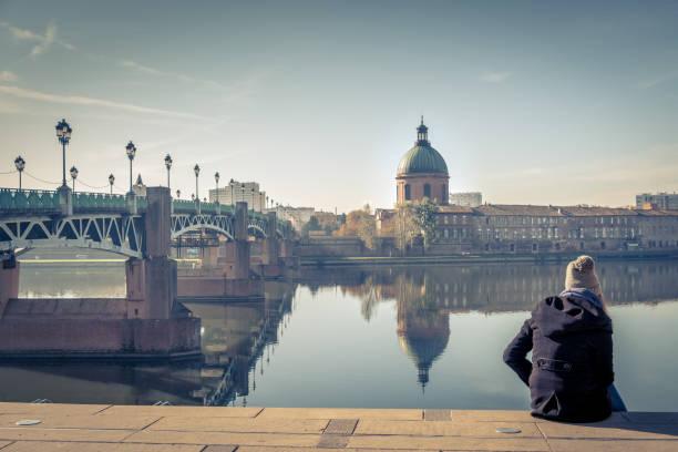 Saint-Pierre Brücke reflektiert in Fluss Garonne und Dome De La Grave mit einer jungen Studentin in Toulouse, Frankreich – Foto