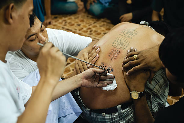 sak yant master macht traditionelle magic tattoo - buddhist tattoos stock-fotos und bilder