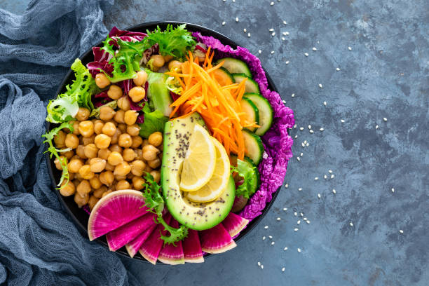 Salad Buddha bowl with fresh cucumber, avocado, watermelon radish, raw carrot, lettuce and chickpea for lunch. Healthy vegetarian food. Vegan vegetable dish. Top view stock photo