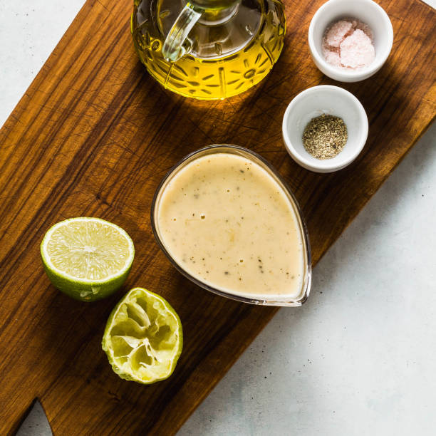 salad dressing of olive oil and lemon juice or lime with seasonings on a cutting wooden board. classic vinaigrette salad dressing of olive oil and lemon juice or lime with seasonings on a cutting wooden board. classic vinaigrette vinaigrette dressing stock pictures, royalty-free photos & images