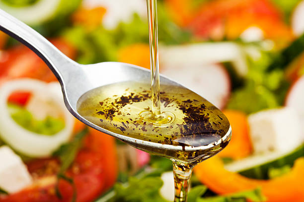 Salad Dressing. Olive oil pouring over salad. salad dressing stock pictures, royalty-free photos & images