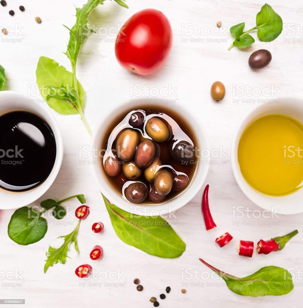 Salad dressings in white bowls with spices, olives and  herbs stock photo