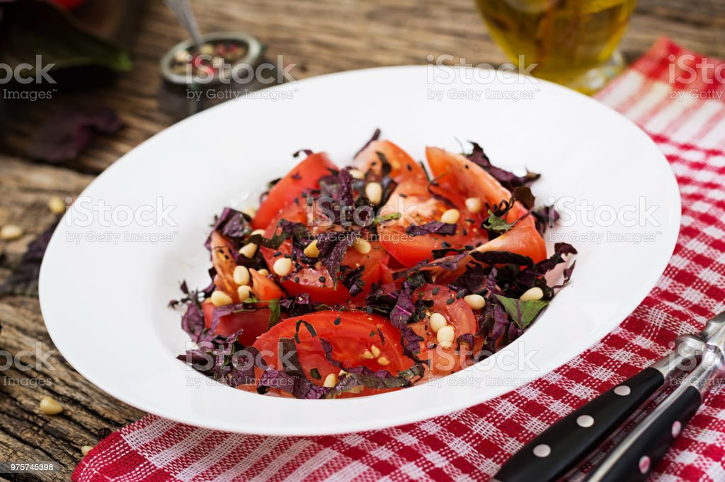 Salat aus Tomaten mit einem violetten Basilikum und Pinienkernen. Veganes Essen. Italienisches Essen. - Lizenzfrei Basilikum Stock-Foto
