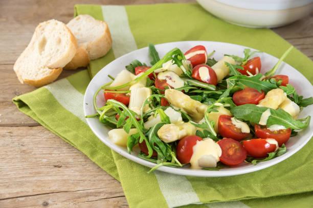 salat von weißem spargel, cocktailtomaten und rugula mit knoblauch-sauce, grüne serviette auf einem rustikalen holztisch - spargel vegan stock-fotos und bilder