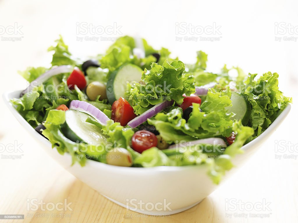 salad in bowl on wood table stock photo