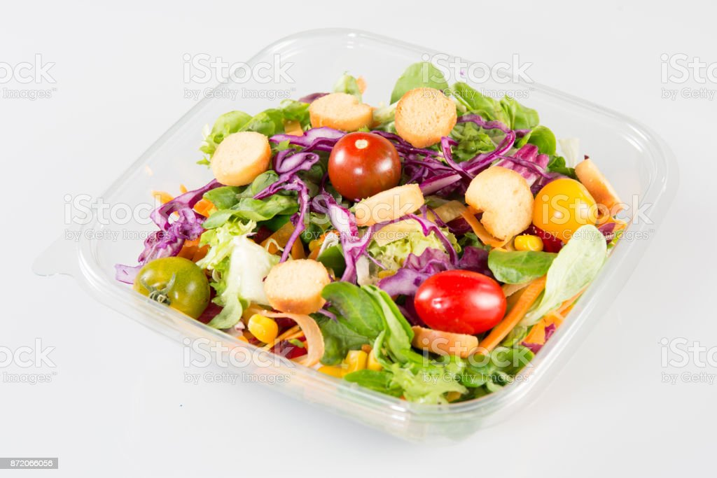 Salad in takeaway container from top on white background stock photo