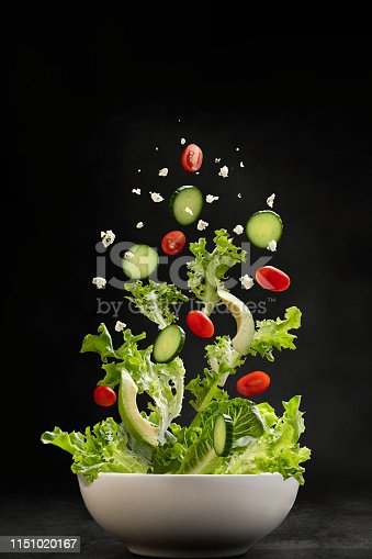 Salad ingredients with servers flying through the air, landing in a bowl