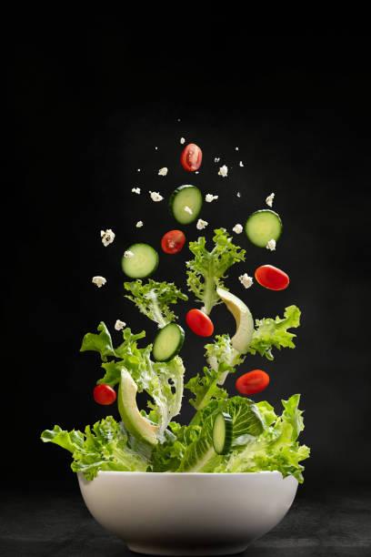 salade ingrediënten vliegen door de lucht, de landing in een kom - salade stockfoto's en -beelden